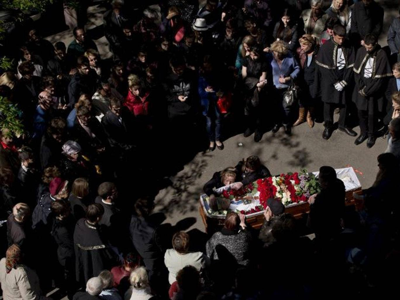 People gather around the coffin of 17 year-old Vadim Papura during a religious service outside the apartment block he lived in, in Odessa, Ukraine, Tuesday, May 6, 2014.