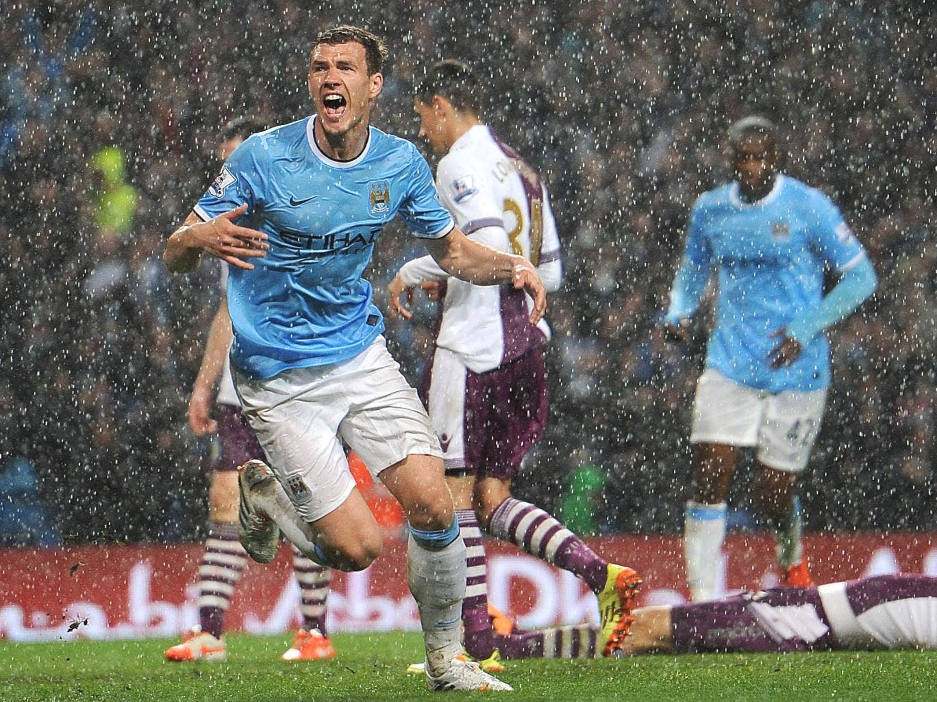 Edin Dzeko turns away after scoring Manchester City's opening goal during a downpour at the Etihad Stadium