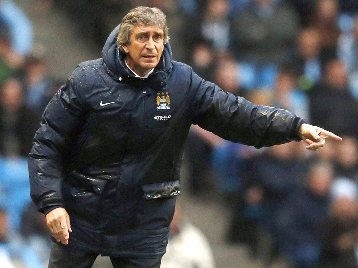 Manchester City boss Manuel Pellegrini urges his troops on