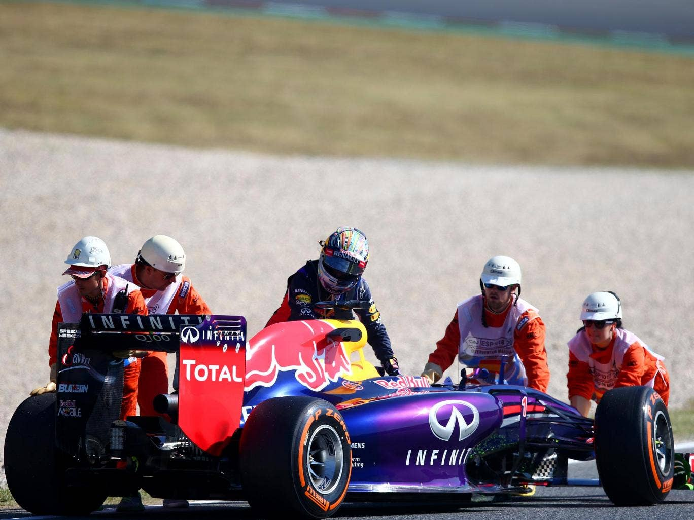 Sebastian Vettel pushes his Red Bull after it grinds to a halt on the Catalunya track