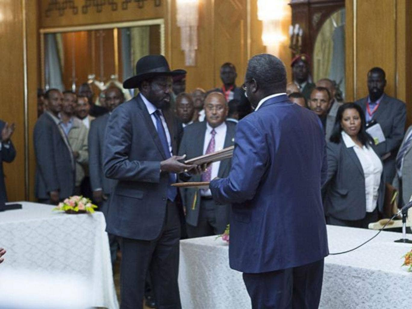 Salva Kiir (L), President of South Sudan, and Riek Machar (R), SPLM Opposition leader, hand over the Cessation of Hostilities treaty over the war in South Sudan