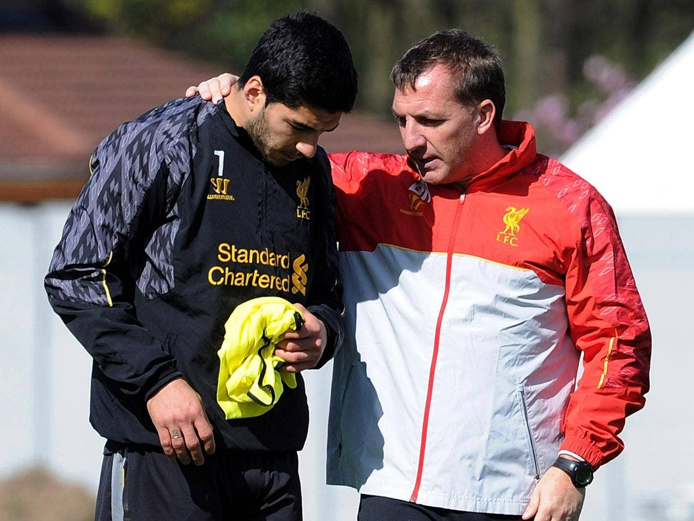Brendan Rodgers talks with Luis Suarez during a Liverpool training session
