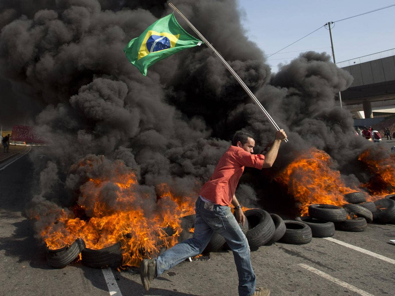 A member of the Homeless Workers Movement carries a Brazilian flag past burning tires during a protest against the money spent on the World Cup near Itaquerao stadium which will host the international soccer tournament's first match in Sao Paulo