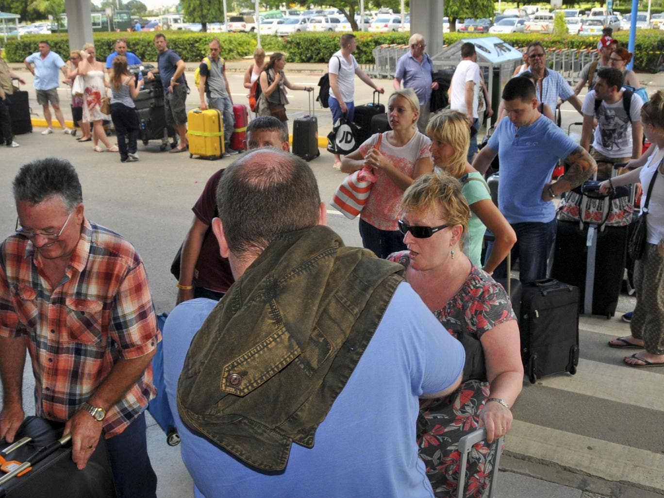 British tourists queue with their luggage to leave by charter flight from the international airport in Mombasa, Kenya