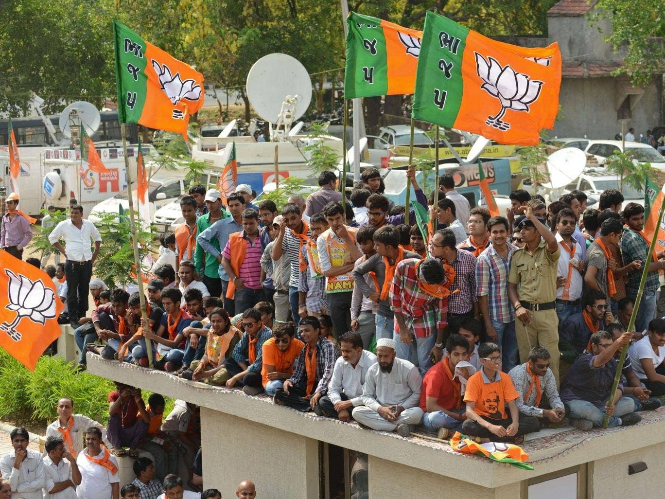 Indian Bharatiya Janata Party (BJP) supporters wait for the arrival of Narendra Modi