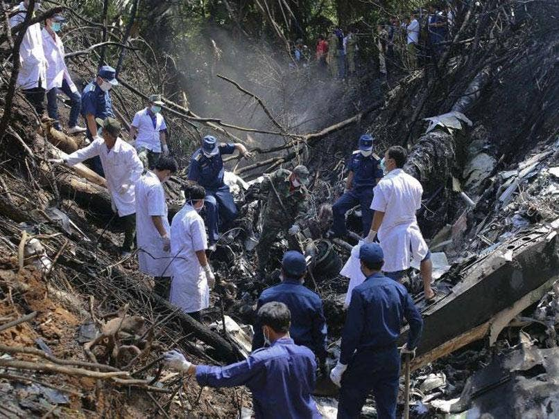 Rescue workers search an air force plane crash site near Nadee village,