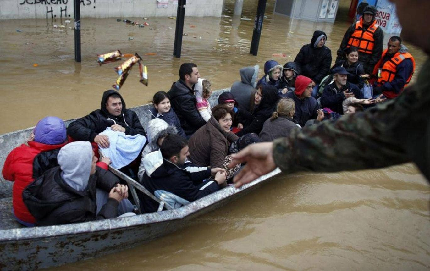 A Serbian army soldier throws candy bars to people on a boat as the flooded town of Obrenovac, east from Belgrade, is evacuated