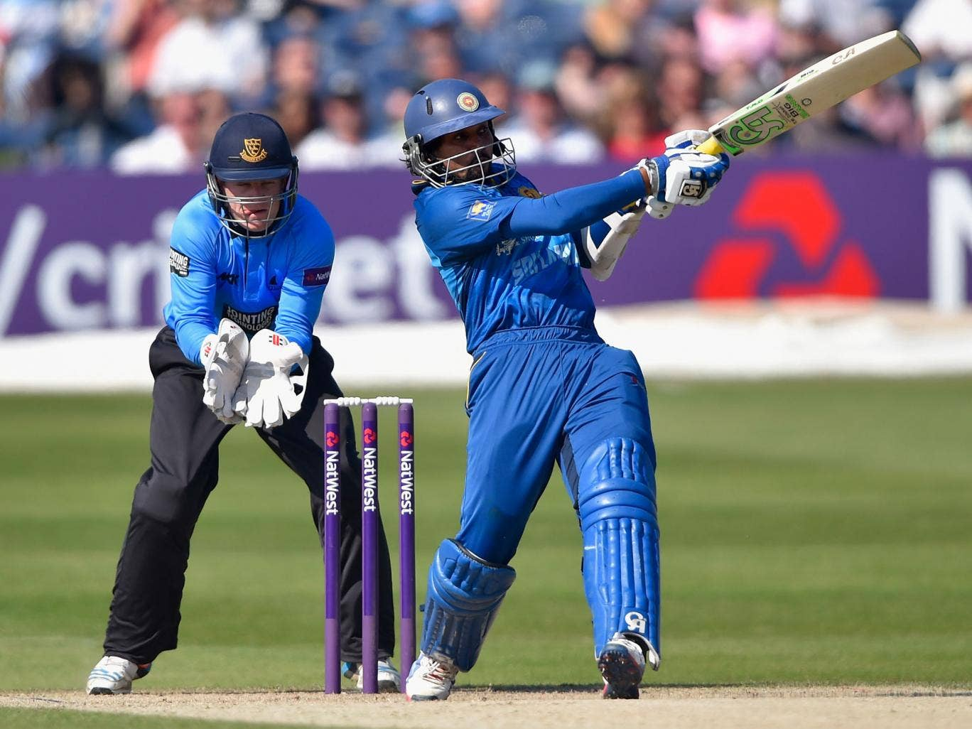 Tillekeratne Dilshan of Sri lanka smashes a boundary as wicketkeeper Ben Brown of Sussex looks on