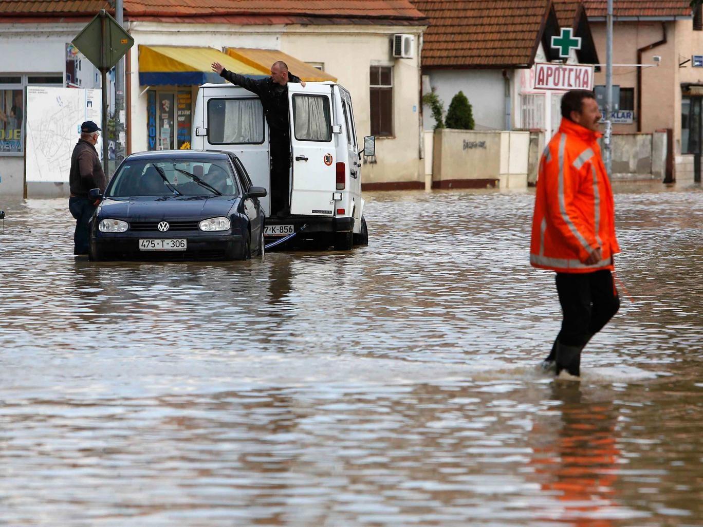 A Bosnian man walks in a flooded street in the Eastern-Bosnian town of Bijeljina