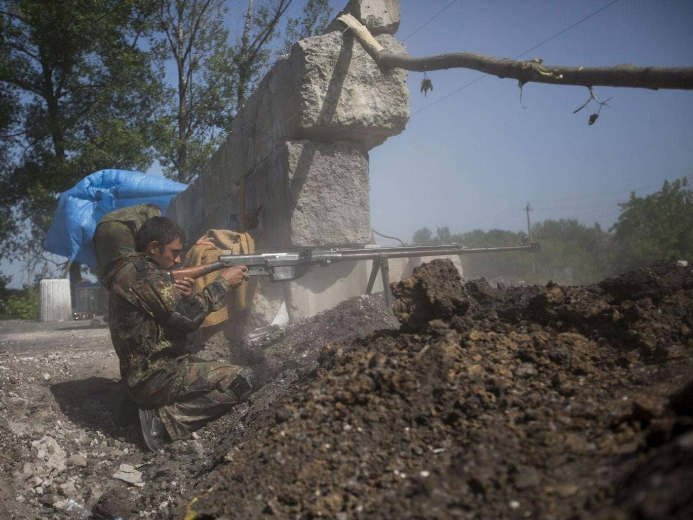 A pro-Russian militant test-fires an anti-tank weapon preparing to fight against Ukrainian government troops at a checkpoint blocking the major highway which links Kharkiv, outside  Slovyansk, eastern Ukraine, Sunday, May 18, 2014. Lawmakers and officials