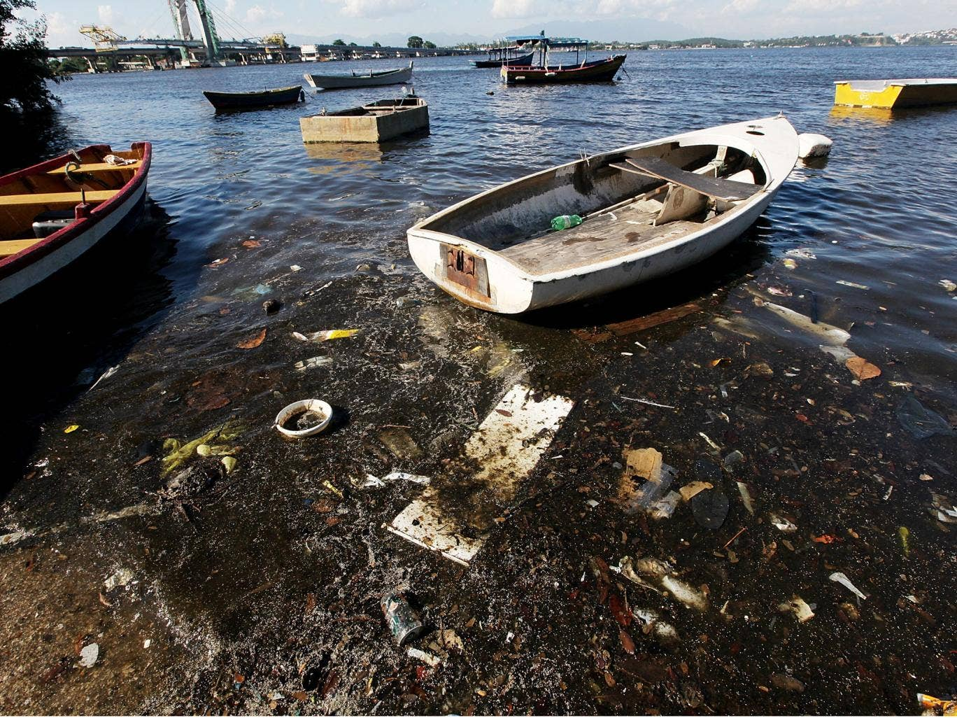 Boats float along the shoreline of the polluted waters of Guanabara Bay
