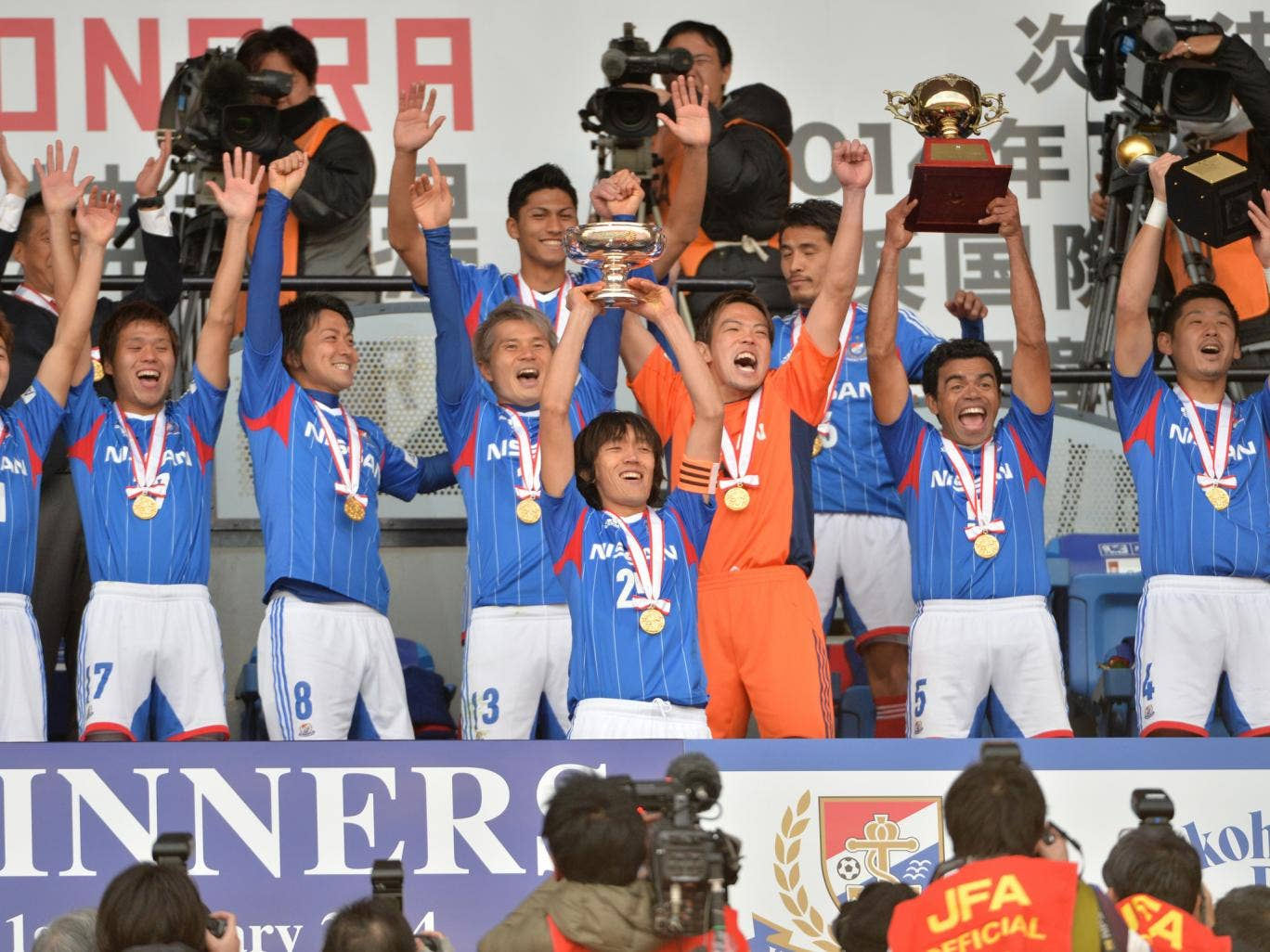 Japan's Yokohama F Marinos captain Shunsuke Nakamura (C, #25) and his teammates celebrate their victory over Sanfrecce Hiroshima during the awards ceremony of the Emperor's Cup final in Tokyo