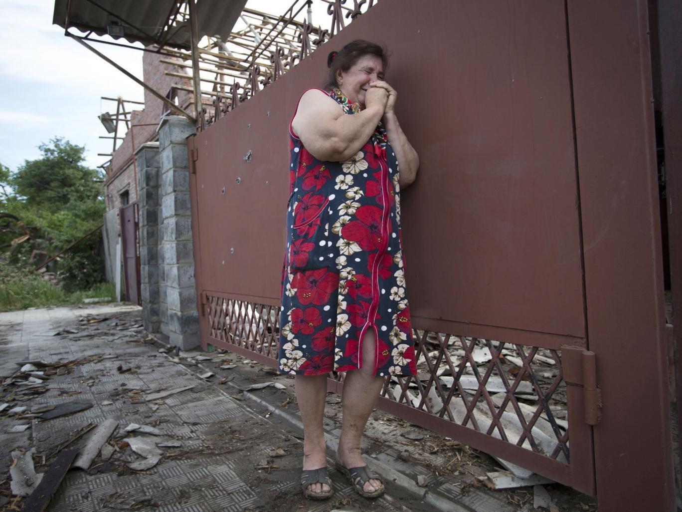 Yekaterina Len (61) cries outside her ruined house in Slavyansk