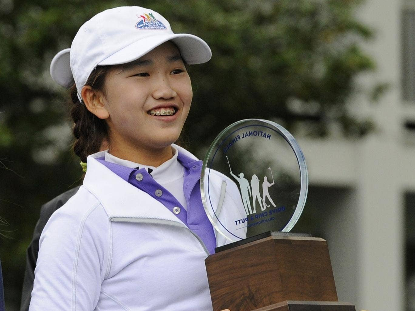 Girls 10-11 category champion Lucy Li from Redwood City, California poses with her trophy during the National Finals of the 2014 Drive, Chip and Putt Championships April 6, 2014 at Augusta National