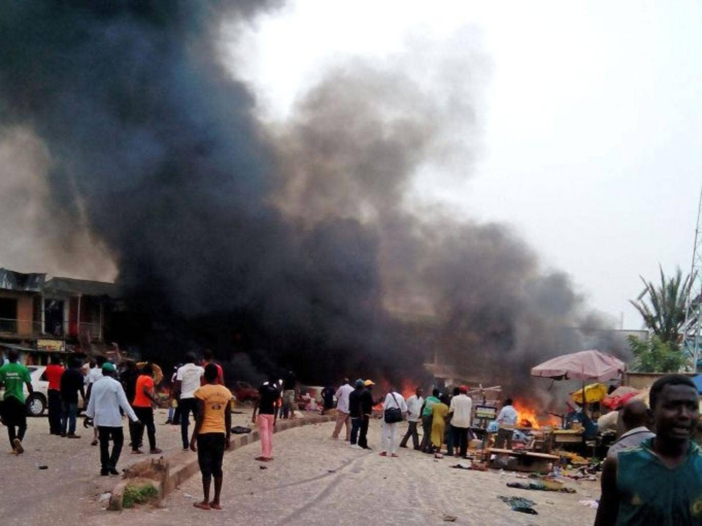Smoke rises after a bomb blast at a bus terminal in Jos, Nigeria, Tuesday, May 20, 2014. Two explosions ripped through a bustling bus terminal and market frequented by thousands of people in Nigeria's central city of Jos on Tuesday afternoon, and police s