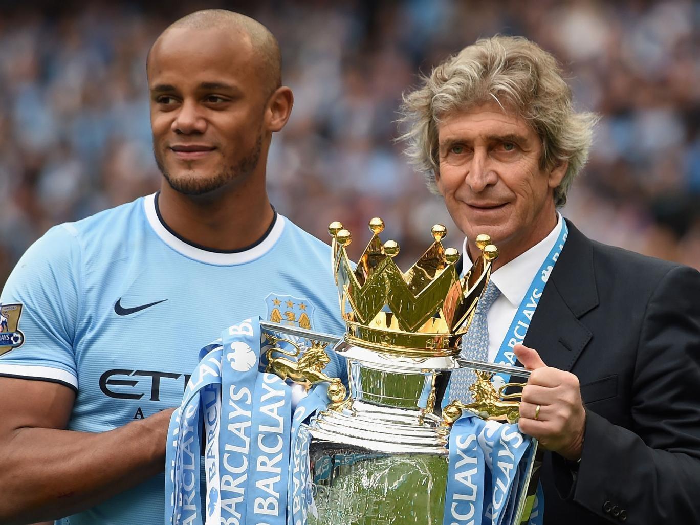 Manchester City manager Manuel Pellegrini holds the Premier League trophy with captain Vincent Kompany