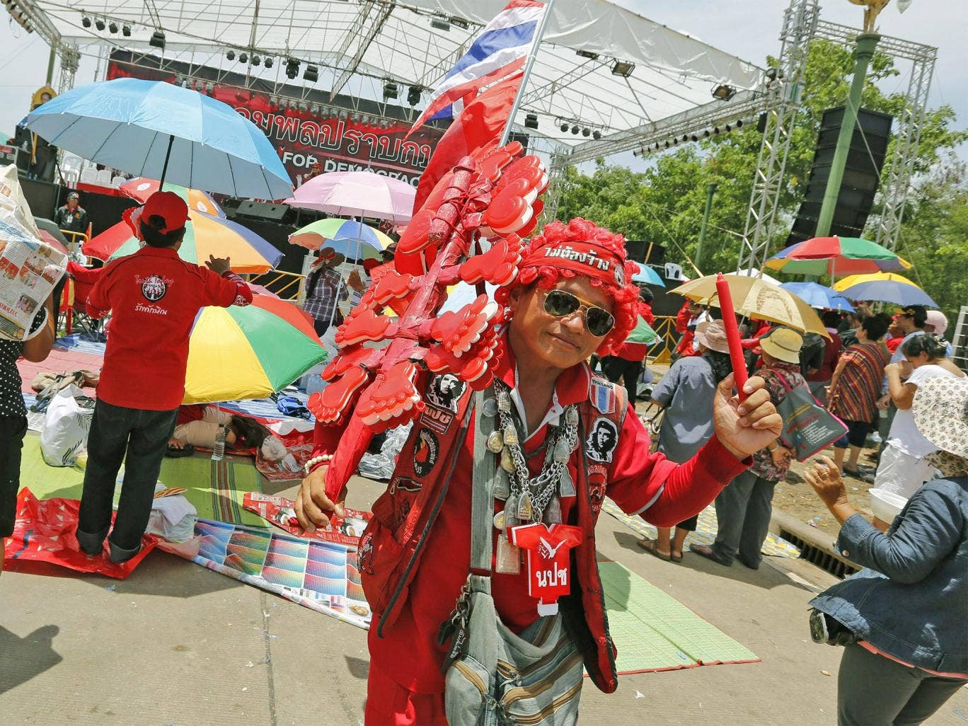 A Thai pro-government Red Shirts protester shakes clapper during a rally on the outskirts of Bangkok
