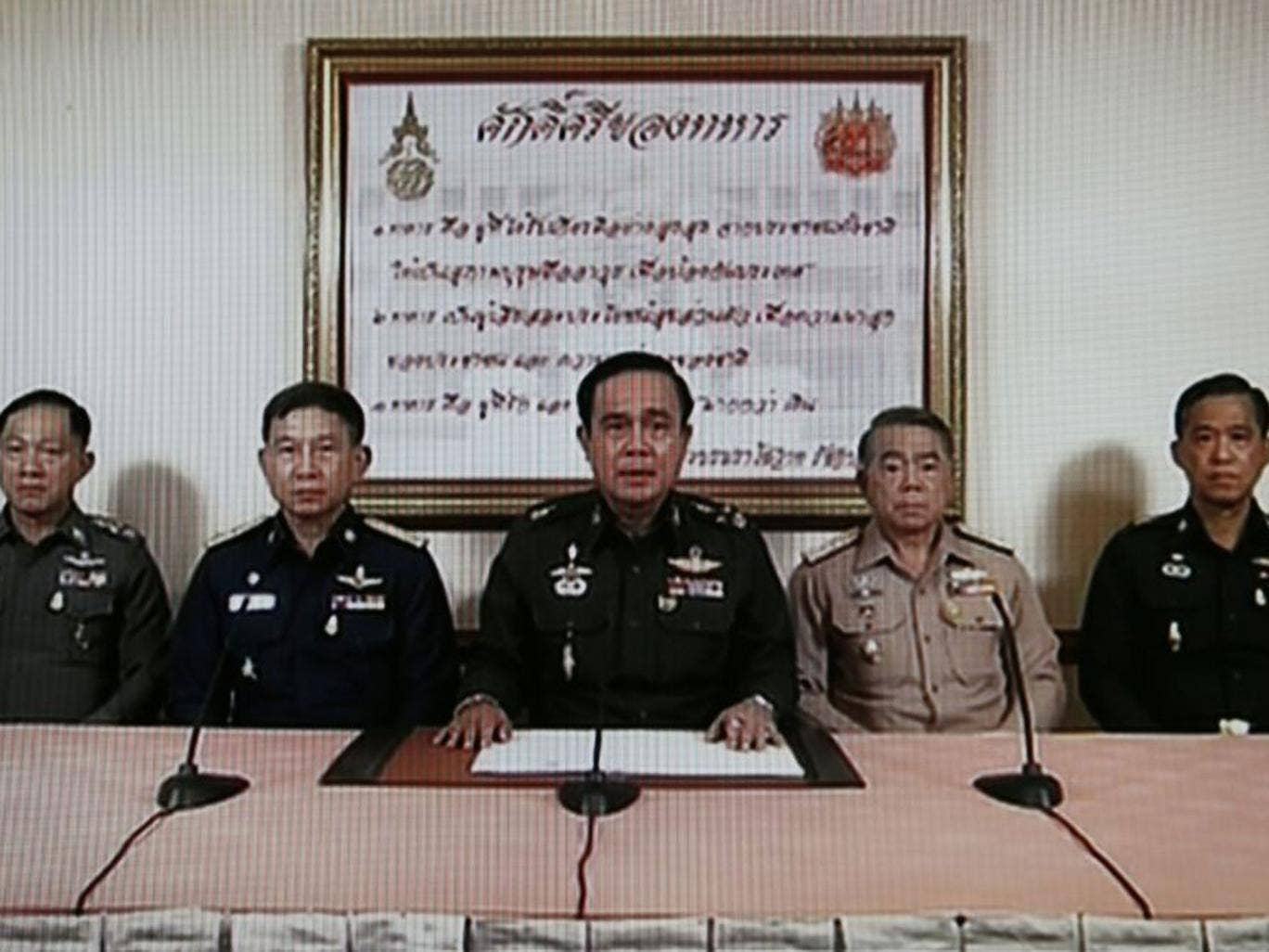 TV grab shows Army Chief General Prayuth Chan-ocha (C) speaking next to Navy Chief Adm Narong Pipattanasai (2-R), Air Chief Marshall Prachin Chantong (2-L), Thai Police Chief Adul Saengsingkaew (L) and identified high rank military officer (R) during a m