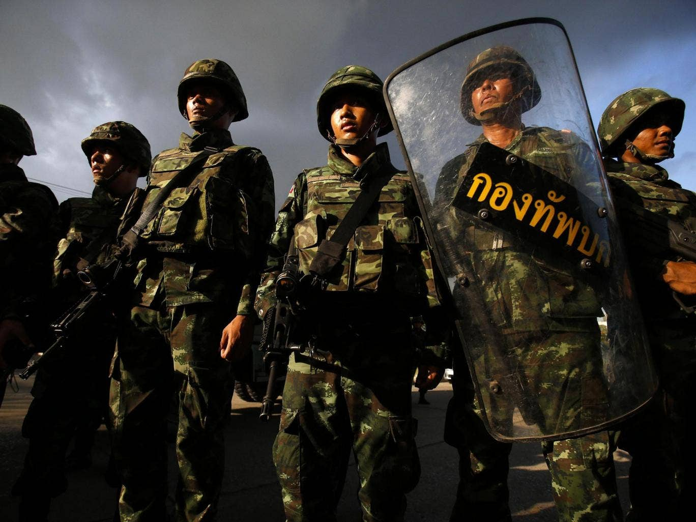 Soldiers stand guard during a coup at the Army Club where Thailand's army chief held a meeting with all rival factions in central Bangkok yesterday