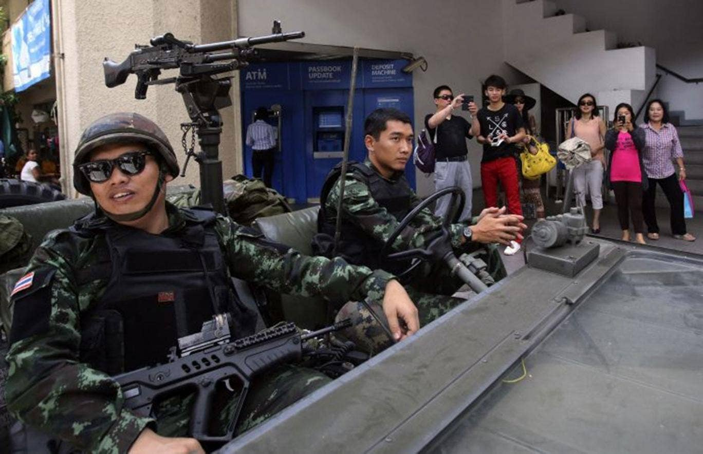 Tourists photograph soldiers outside the Thai police headquarters in Bangkok