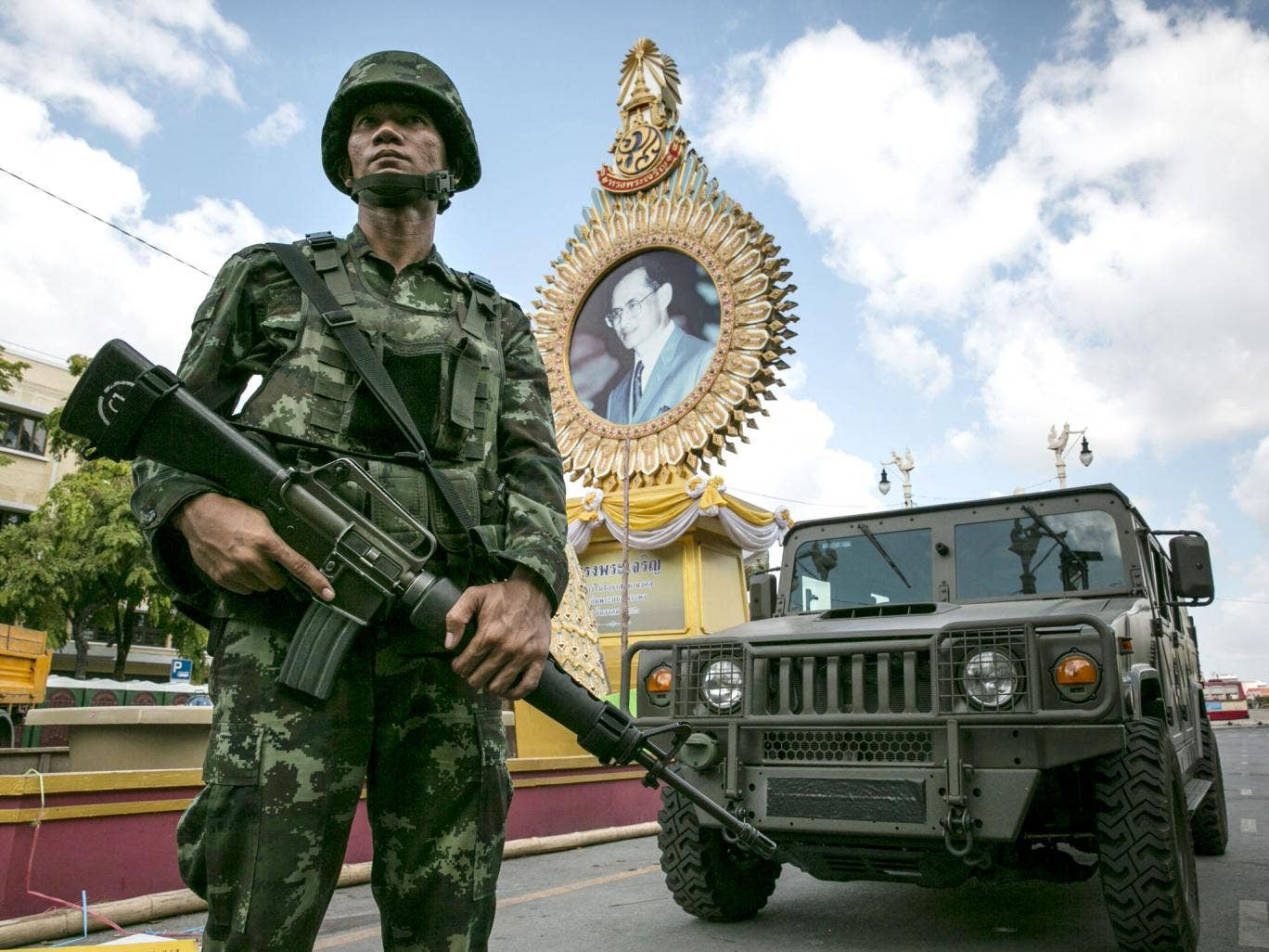 A Thai soldier stands in front of a portrait of Thai King Bhumibol Adulyadej as he patrols near government  buildings in Bangkok