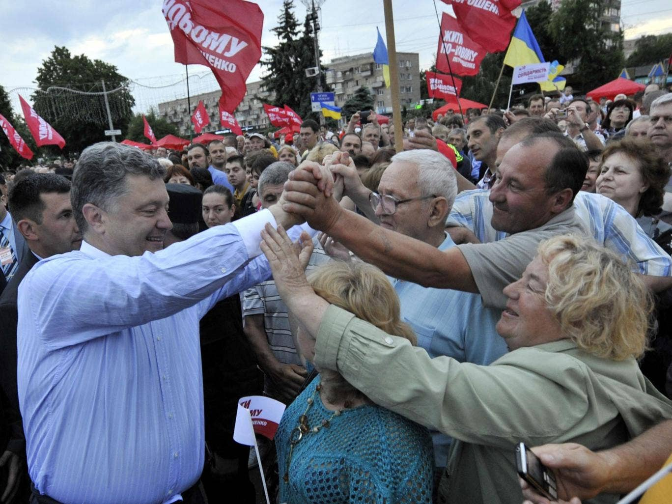 This handout picture released by the Poroshenko press service shows Ukrainian independent presidential candidate Petro Poroshenko (L) being greeted by supporters