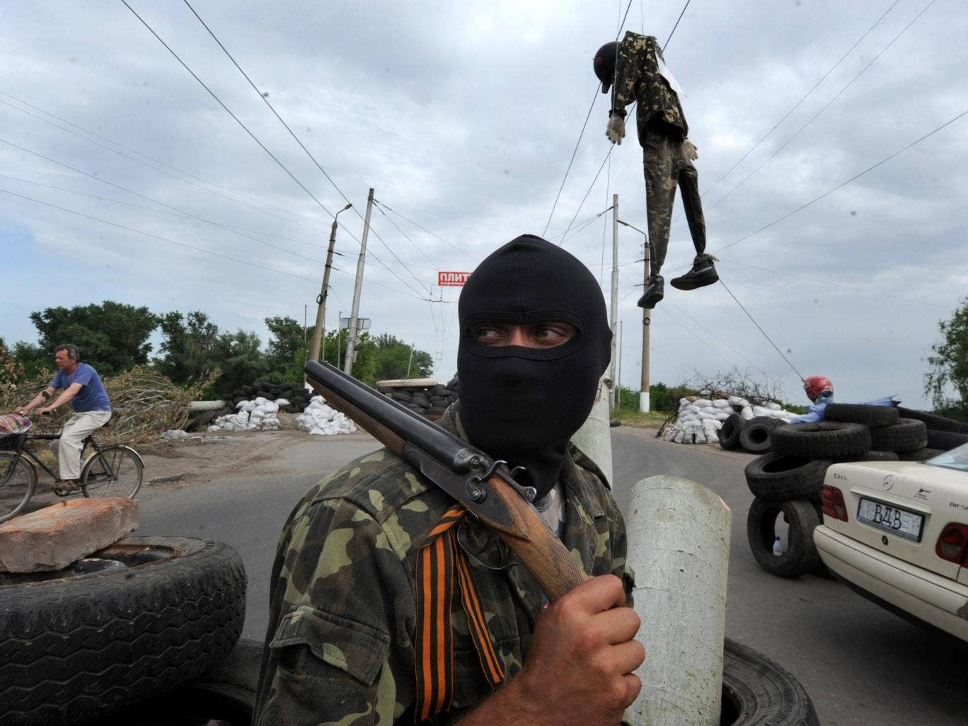 A masked pro-Russian gunman guards at a check-point near the eastern Ukrainian city of Slavyansk on Friday. At least five were killed yesterday in fighting near Ukraine's eastern hub of Donetsk