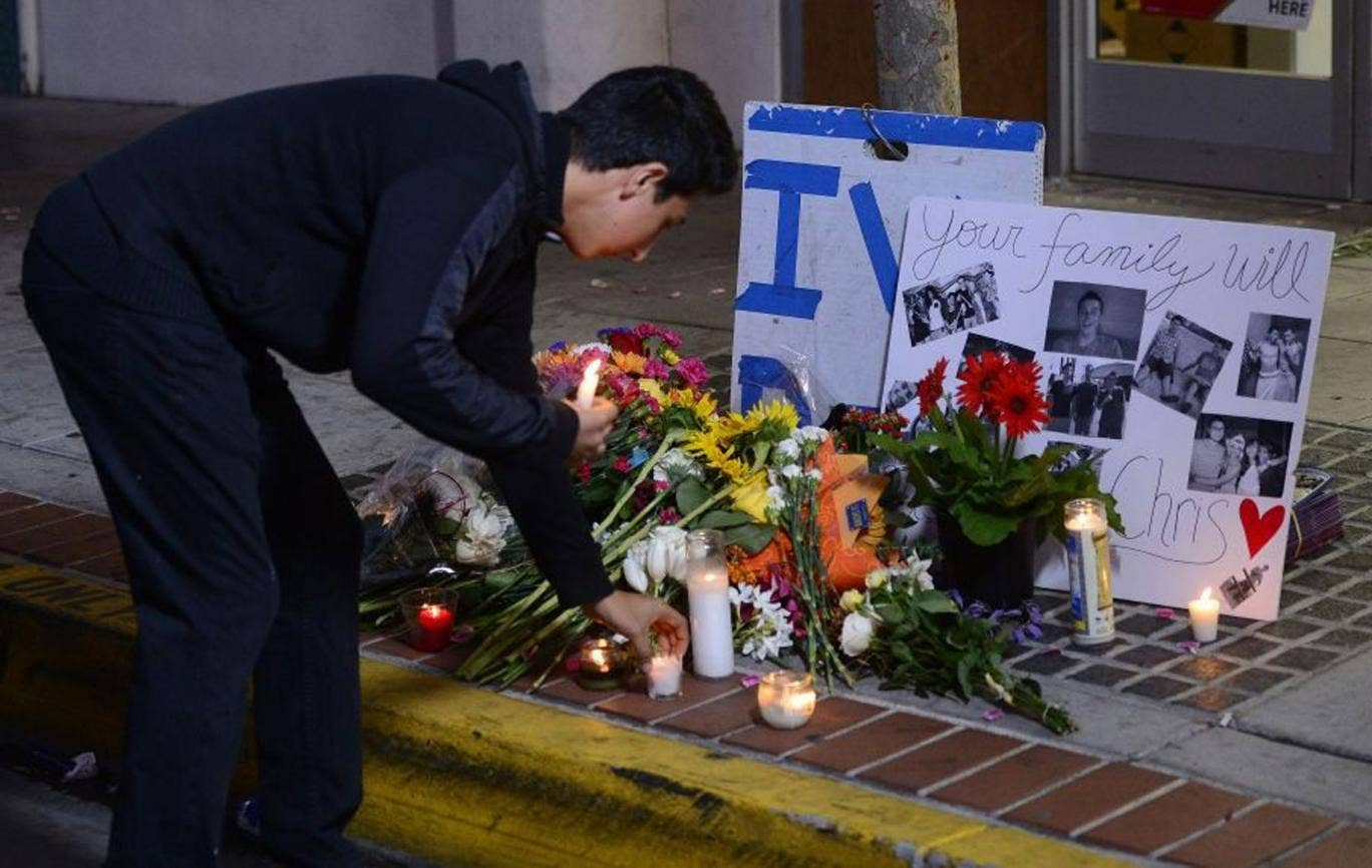 A man places a candle at a makeshift memorial next to the Isla Vista Deli Mart where one of the victims of the deadly shooting rampage was killed at the University of California at Santa Barbara (UCSB) college town of Isla Vista, California