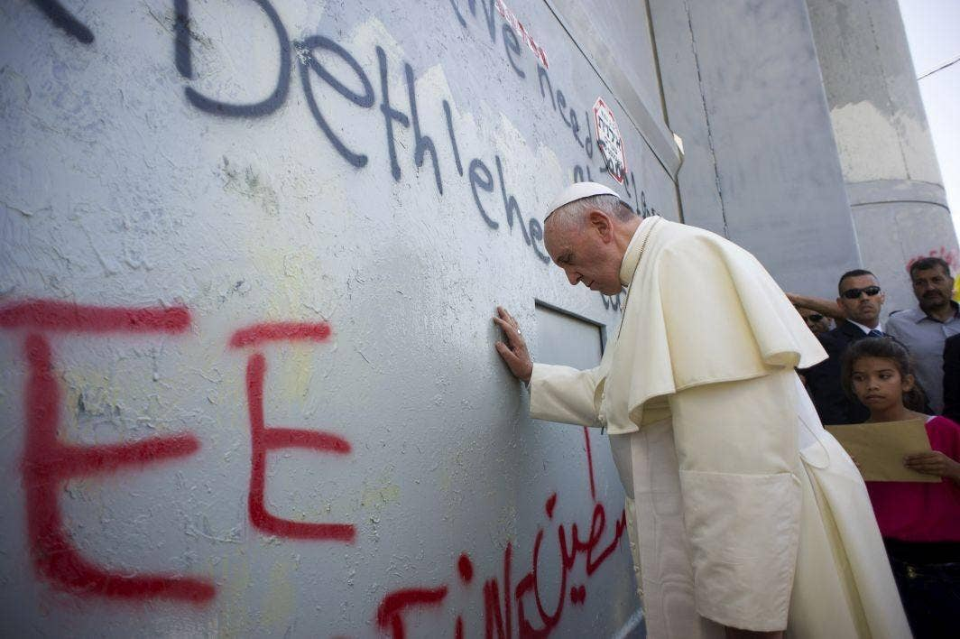 Pope Francis prays at the wall that divides Israel from the West Bank, on his way to celebrate a mass in Manger Square in Bethlehem