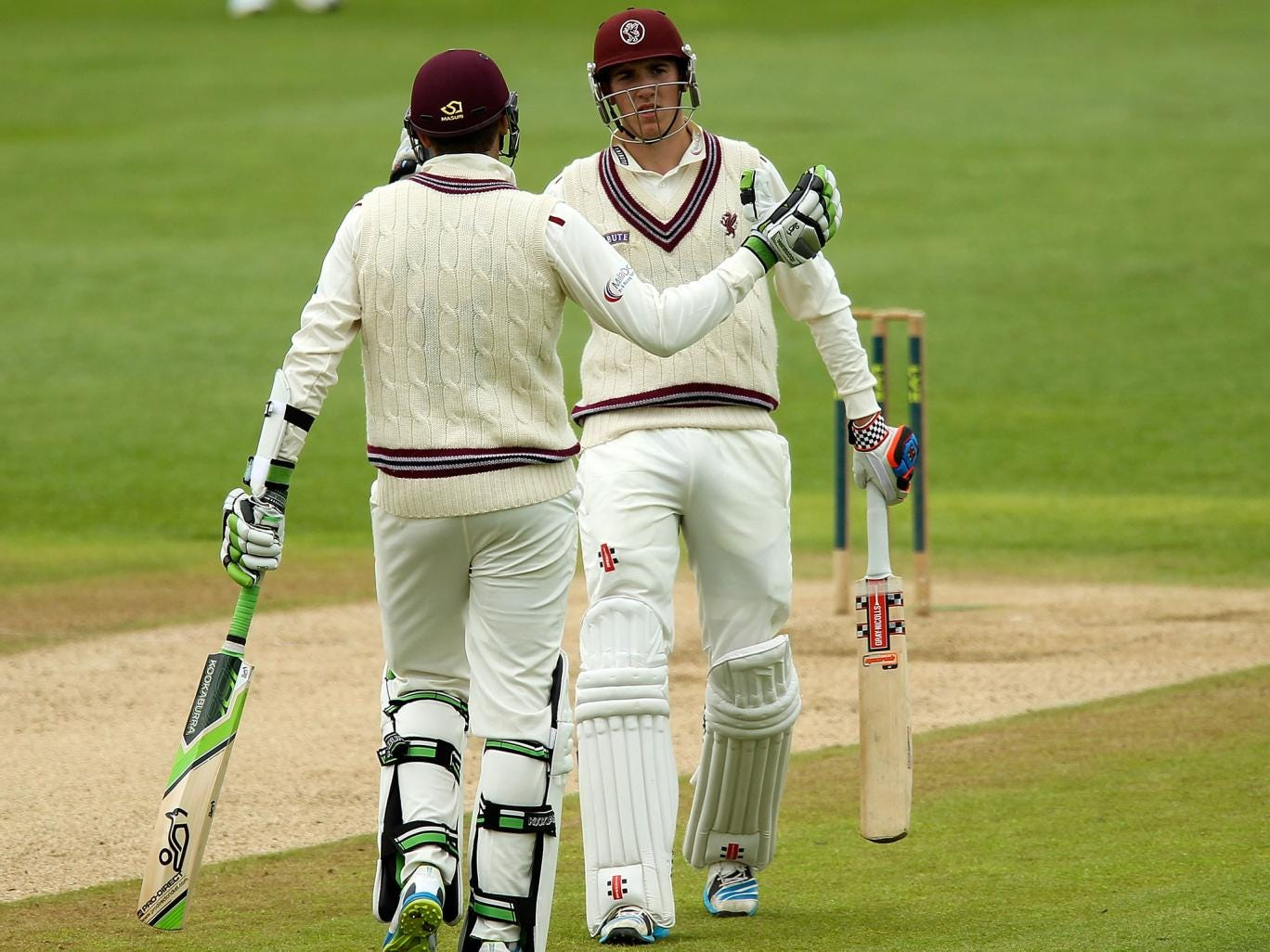 Jamie Overton of Somerset is congratulated by his brother, Craig, after hitting a maiden half-century