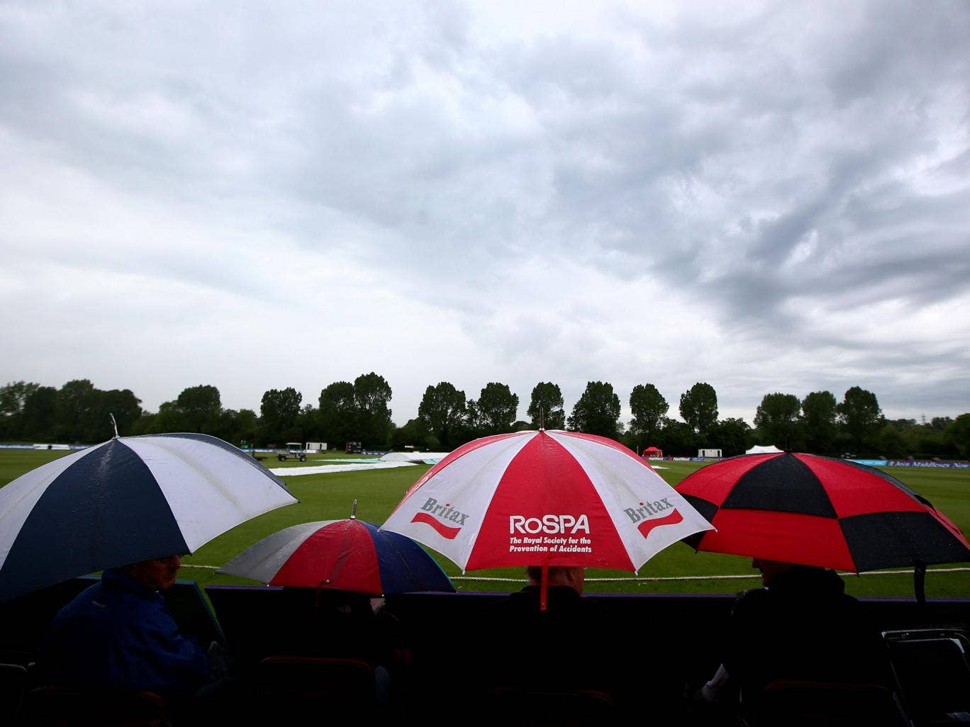 Spectators take shelter as the rain covers come on and the start of play is delayed during the LV County Championship match between Middlesex and Sussex on 26 May in Northwood, England