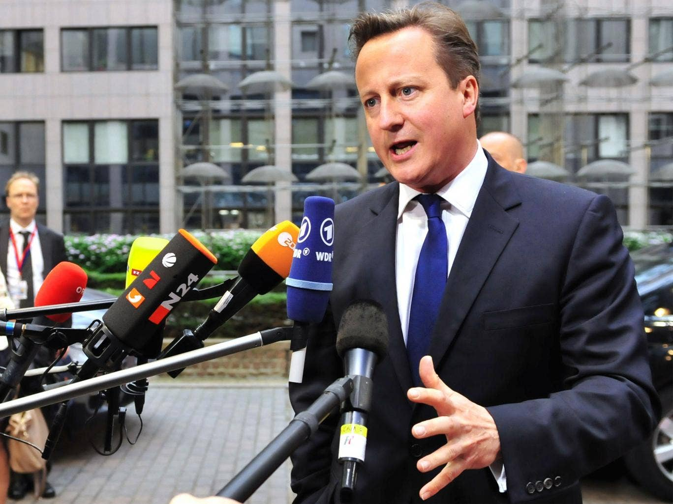 Prime Minister Cameron speaks to media as he arrives in Brussels