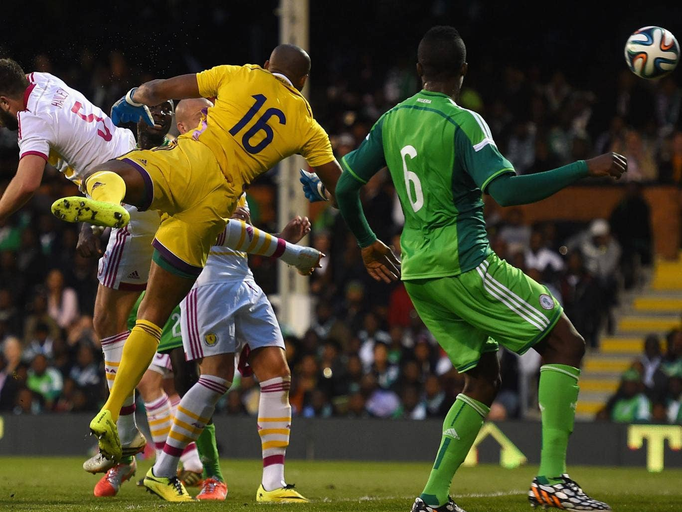 Nigeria goalkeeper Austine Ejide (#16) scoops the ball into his own net while competing with Scotland's Grant Hanley (#5)