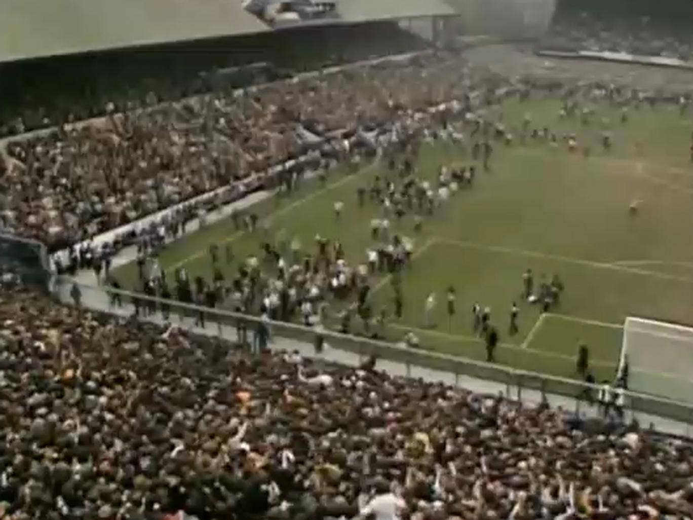 Crowds run across the pitch during the match
