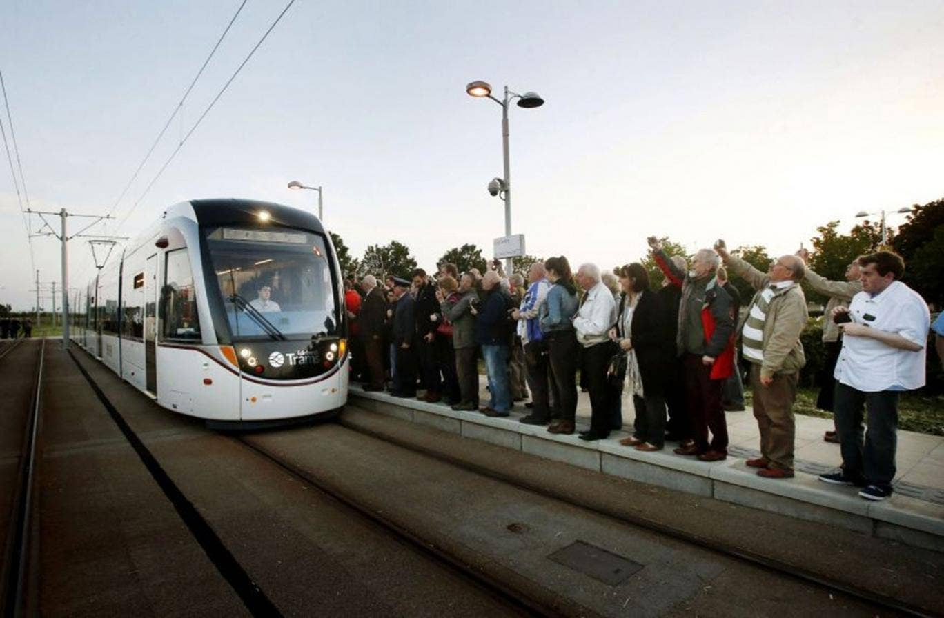 Passengers wait to board the first tram at the Gyle shopping centre stop in Edinburgh