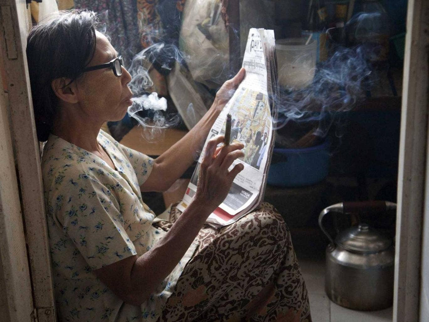 A woman in Burma reads the paper while smoking