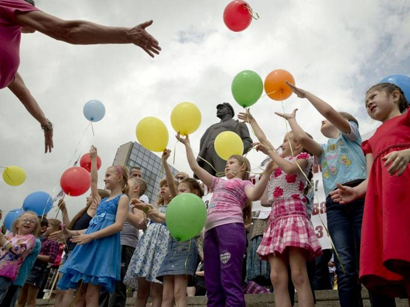 Children release balloons, back dropped by a statue of Lenin, during a pro-Russian rally in Donetsk, Ukraine, Sunday, June 1, 2014. On Saturday, Russiaís Foreign Ministry criticized a suggestion by an official from the Organization for Security and Cooper