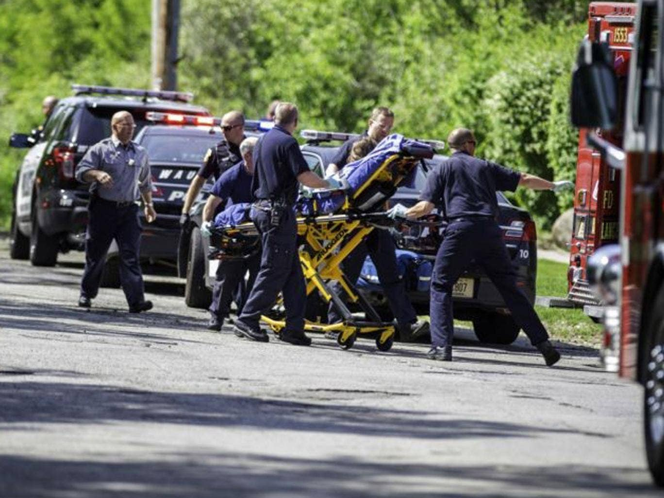 Rescue workers take a stabbing victim to the ambulance in Waukesha, Wis. Prosecutors say two 12-year-old southeastern Wisconsin girls stabbed their 12-year-old friend nearly to death in the woods to please a mythological creature they learned about online
