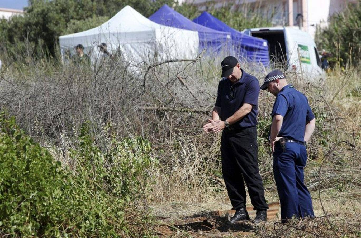 British police search scrubland next to a newly-erected tent in the search for Madeleine McCann