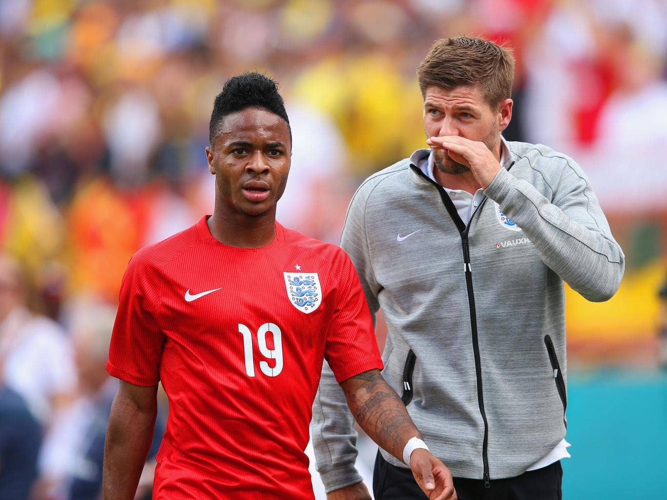 Raheem Sterling walks off the pitch in Miami alongside Steven Gerrard after being sent off for a tackle on Antonio Valencia
