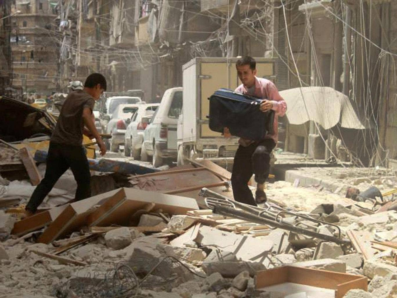 A man carries his bag as he walks on the debris of a damaged building which was attacked by a government forces airstrike, in Aleppo, Syria