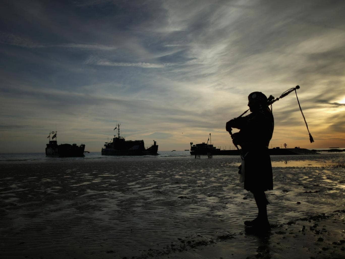 A piper plays a lament on Gold Beach as Royal Marines landing craft arrive at Arromanche at the start of yesterday's D-Day commemorations