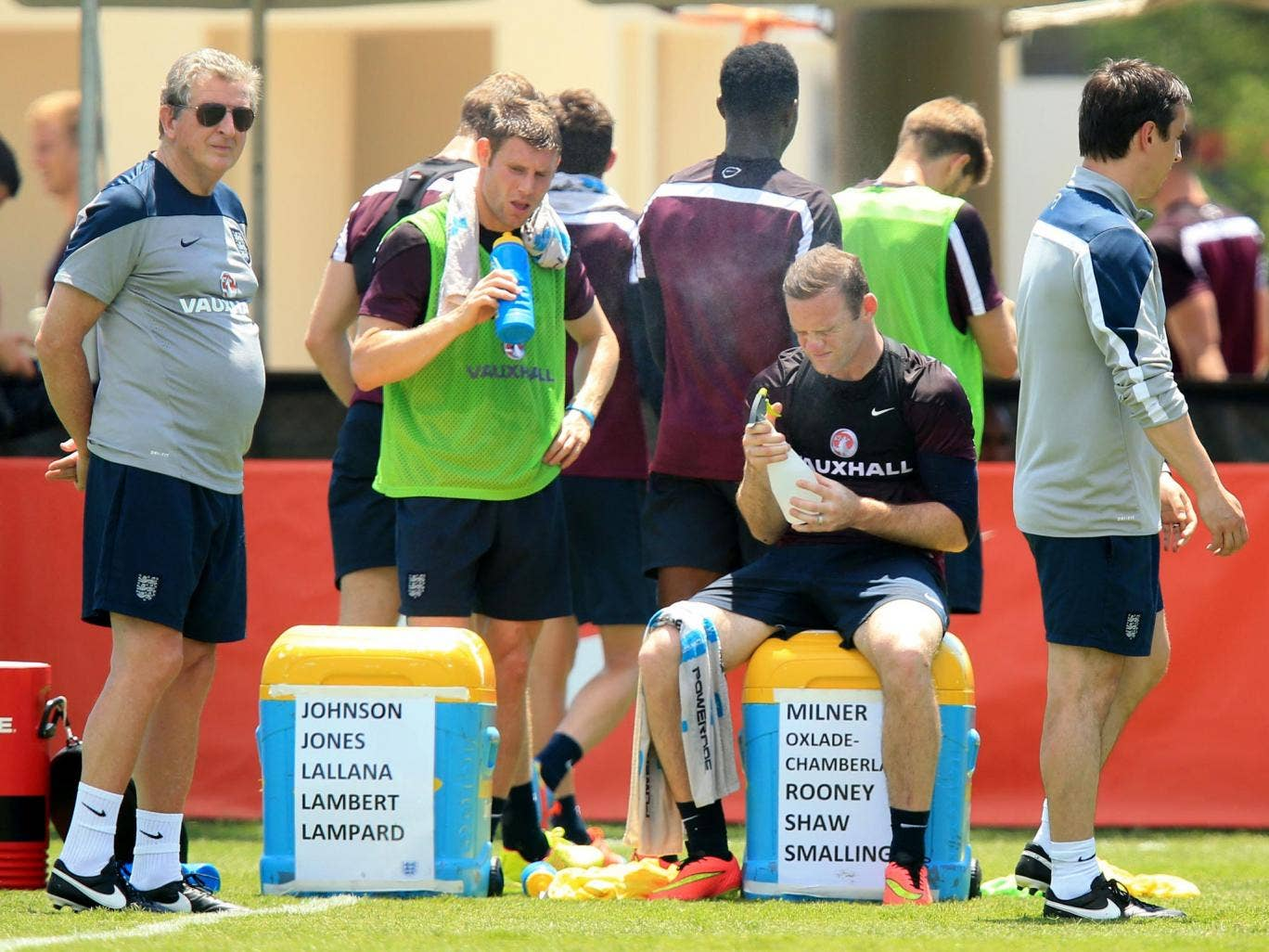 Wayne Rooney (right) and James Milner feel the heat as Roy Hodgson looks on during England training yesterday