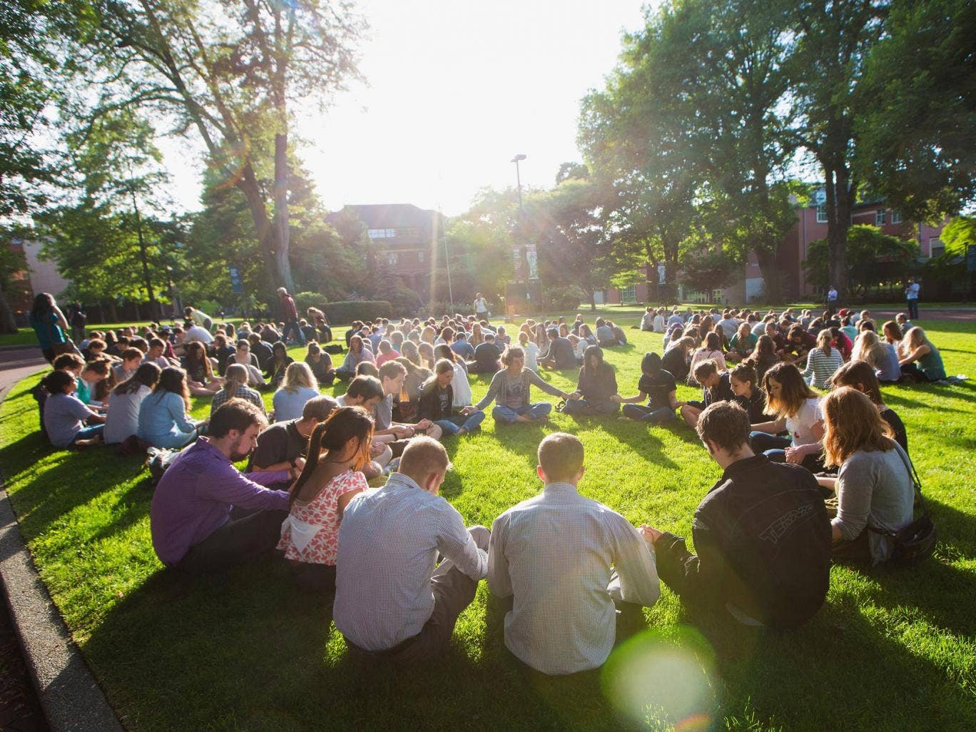 Students link hands and pray on the campus lawns of Seattle Pacific University, where Thursday's fatal shooting took place