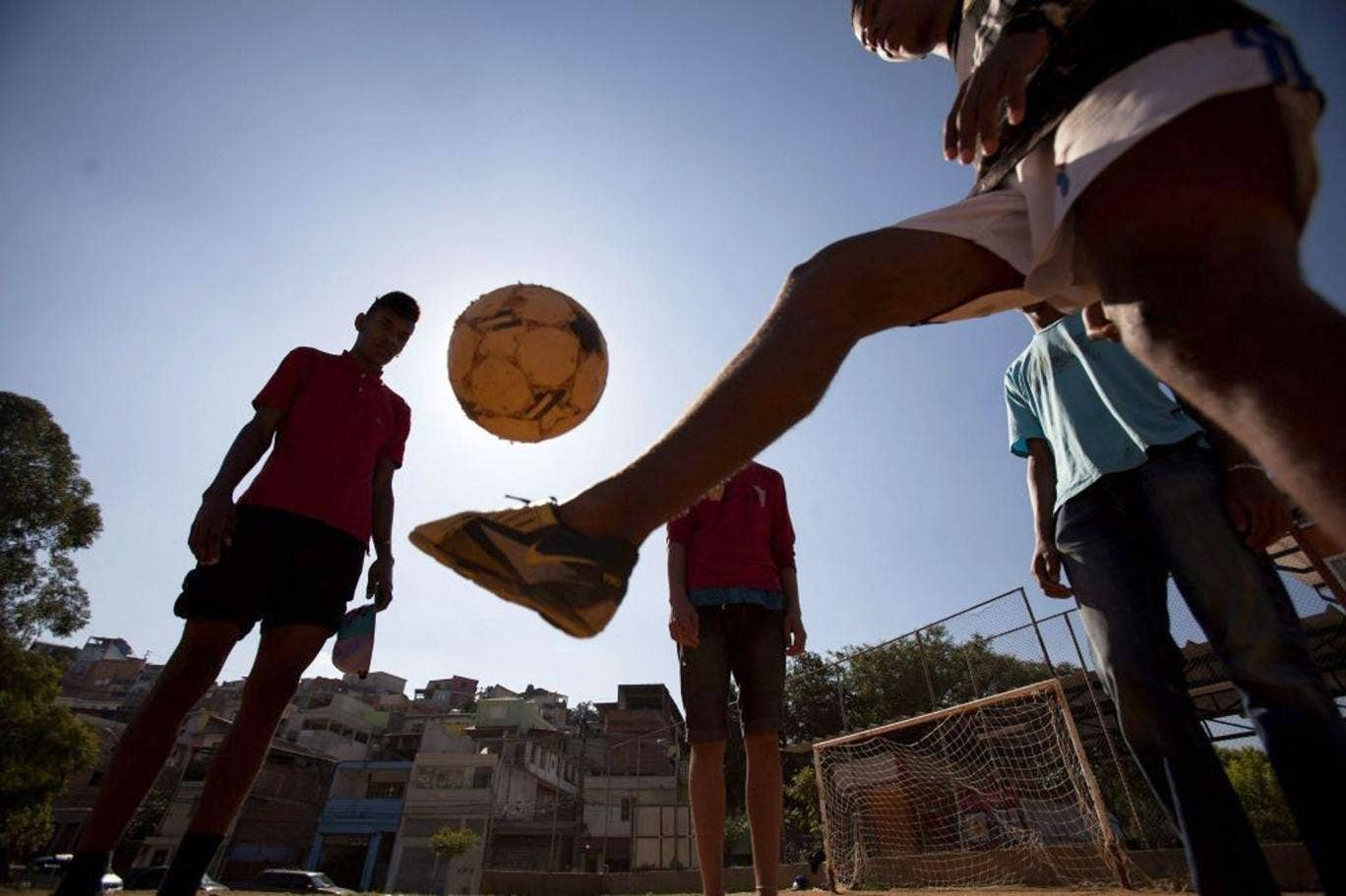 Nearly time for kick off: Young Brazil fans playing football on the outskirts of Sao Paulo