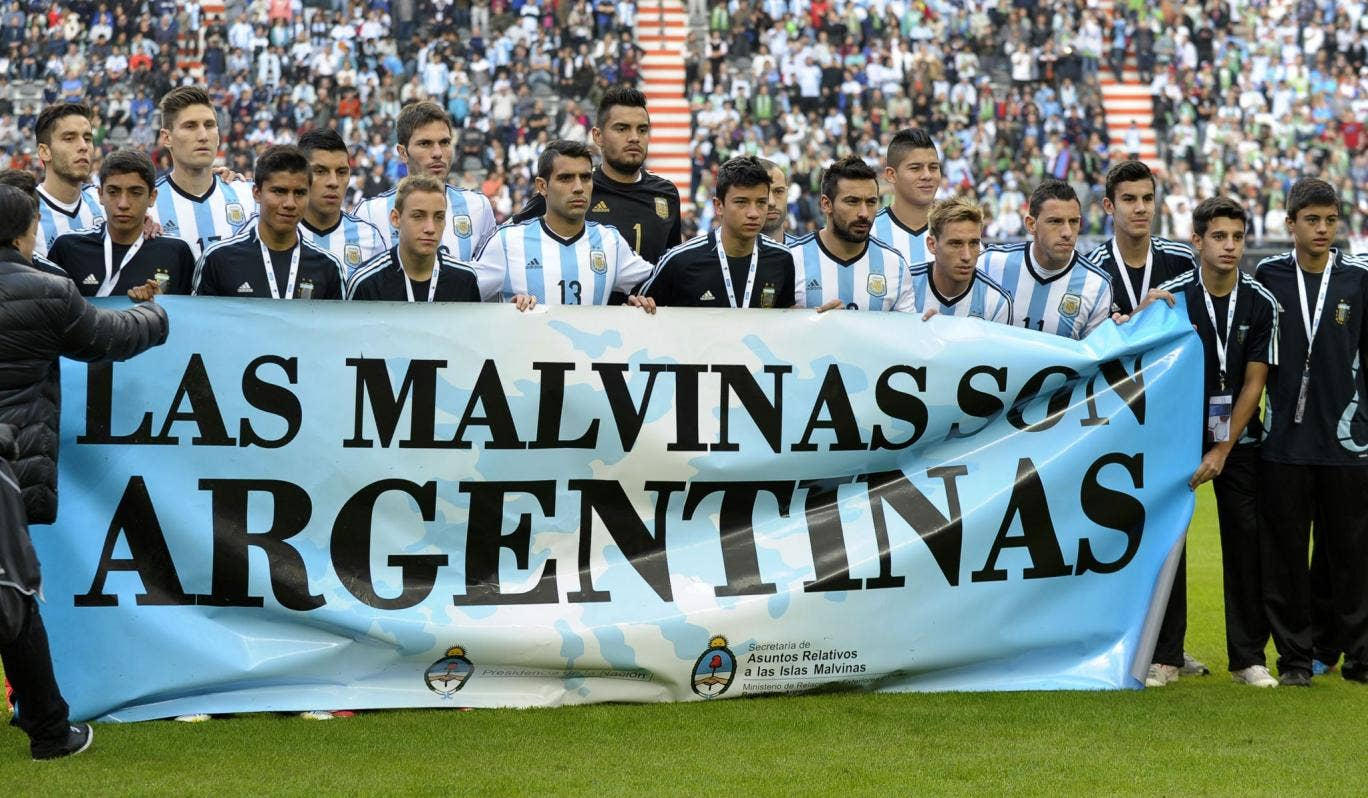"""Argentina's footballers pose for photographers holding a banner reading """"The Malvinas are Argentinian"""" before a friendly against Slovenia at La Plata stadium in Buenos Aires"""