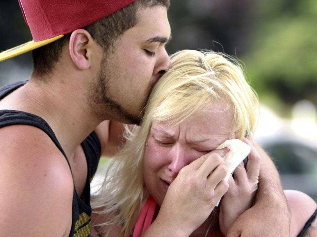 Two people comfort each other as they await word about the safety of students after a shooting at Reynolds High School, Tuesday, June 10, 2014, in Troutdale, Ore. A gunman killed a student at the high school east of Portland Tuesday and the shooter is als