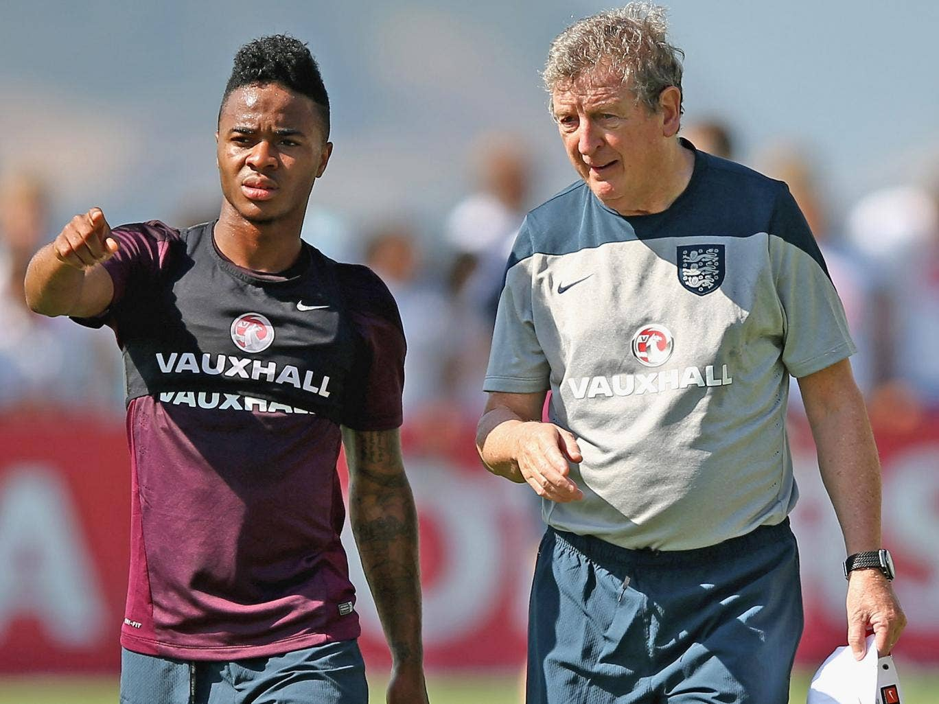 Raheem Sterling talks with manager Roy Hodgson during an England training session