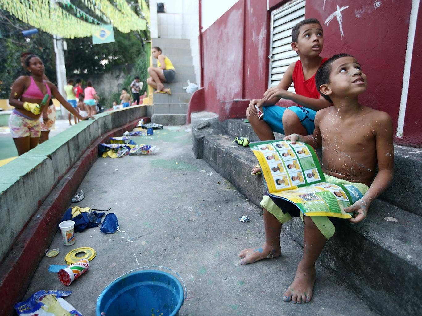 Brazilians gather while painting a section of the Santa Marta shantytown, or 'favela', in Brazilian colors as a boy holds his Panini World Cup stickers book