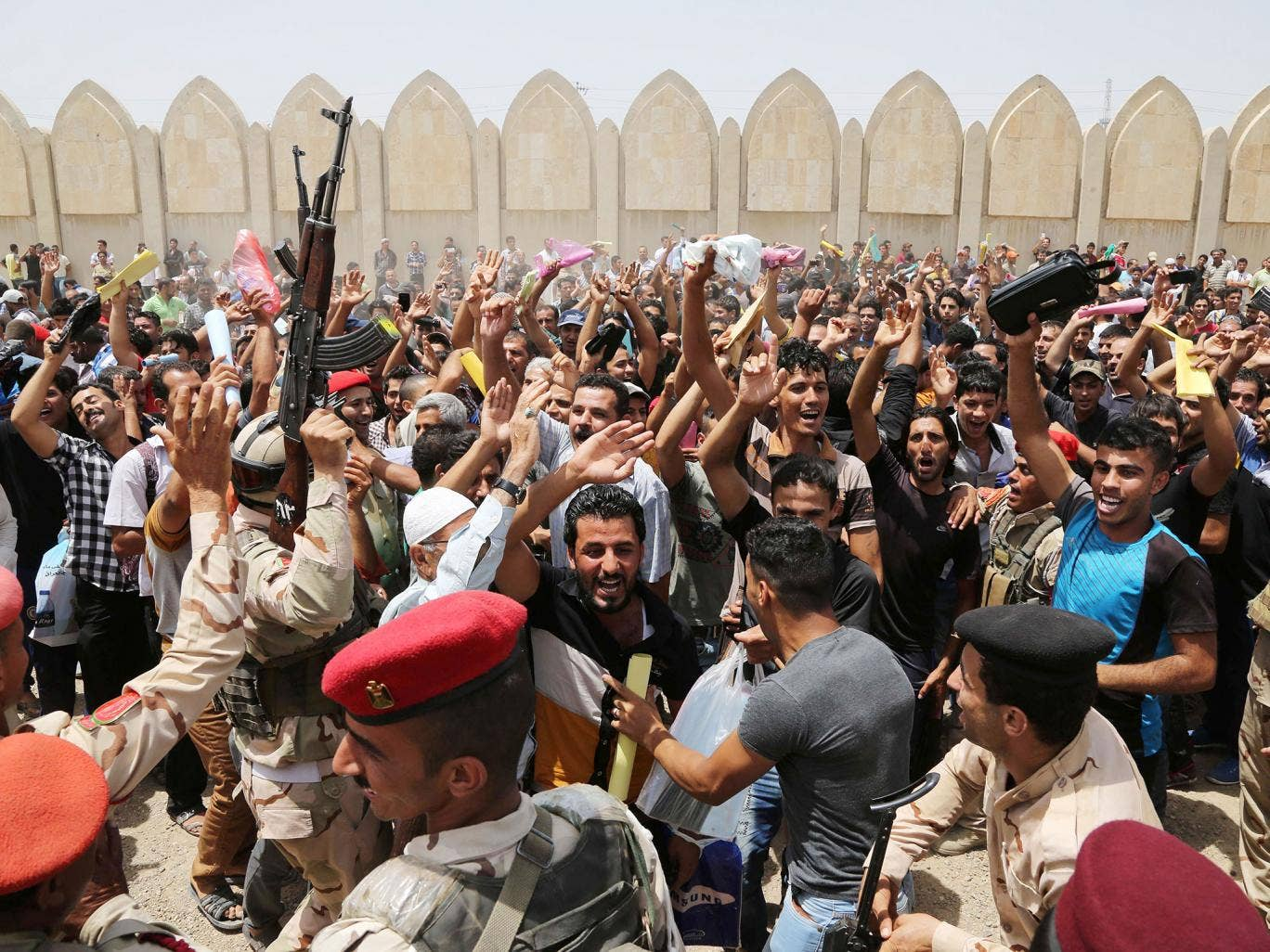 Young men in Baghdad chant slogans against Isis outside the main army recruiting centre yesterday, where they are volunteering to fight the extremist group